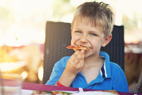 Cute little boy eating pizza